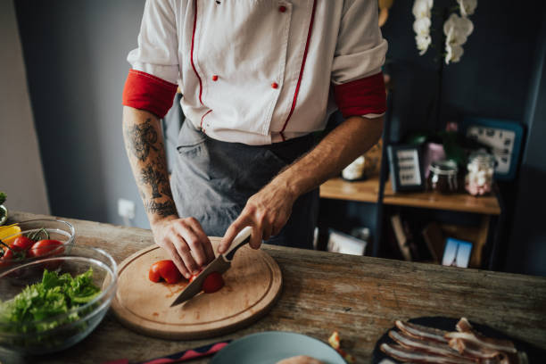 tätowierte chef schneidet tomaten in runde scheiben - essen tattoos stock-fotos und bilder