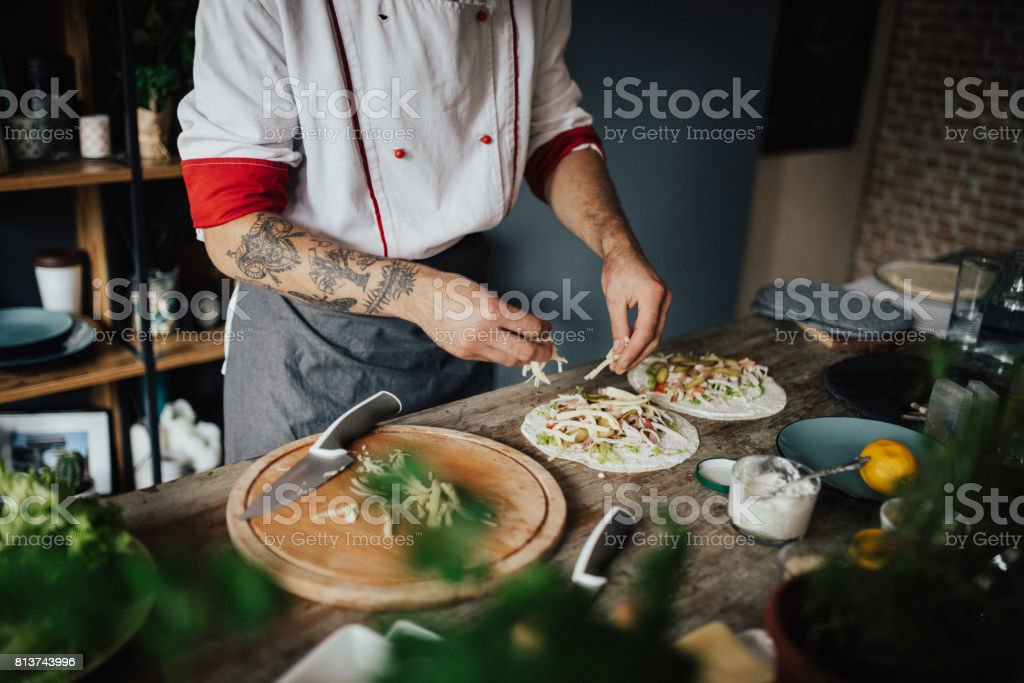 Tattooed chef is making wrap sandwiches stock photo