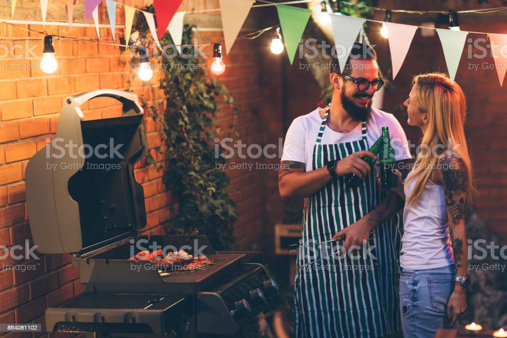 Tattooed Couple At Barbecue In Backyard royalty-free stock photo