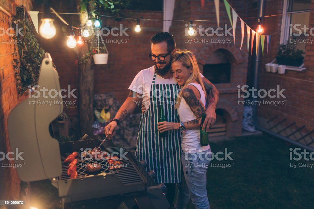 Tattooed Couple Having Fun At Barbecue In Backyard royalty-free stock photo