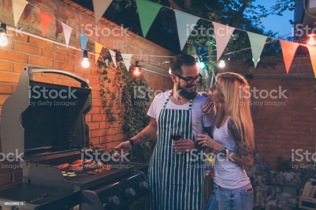 Tattooed Couple Having Fun At Barbecue In Backyard royalty-free stock photo
