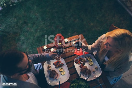 istock Tattooed Couple Having Romantic Backyard Barbecue Dinner With Proposal 864097168