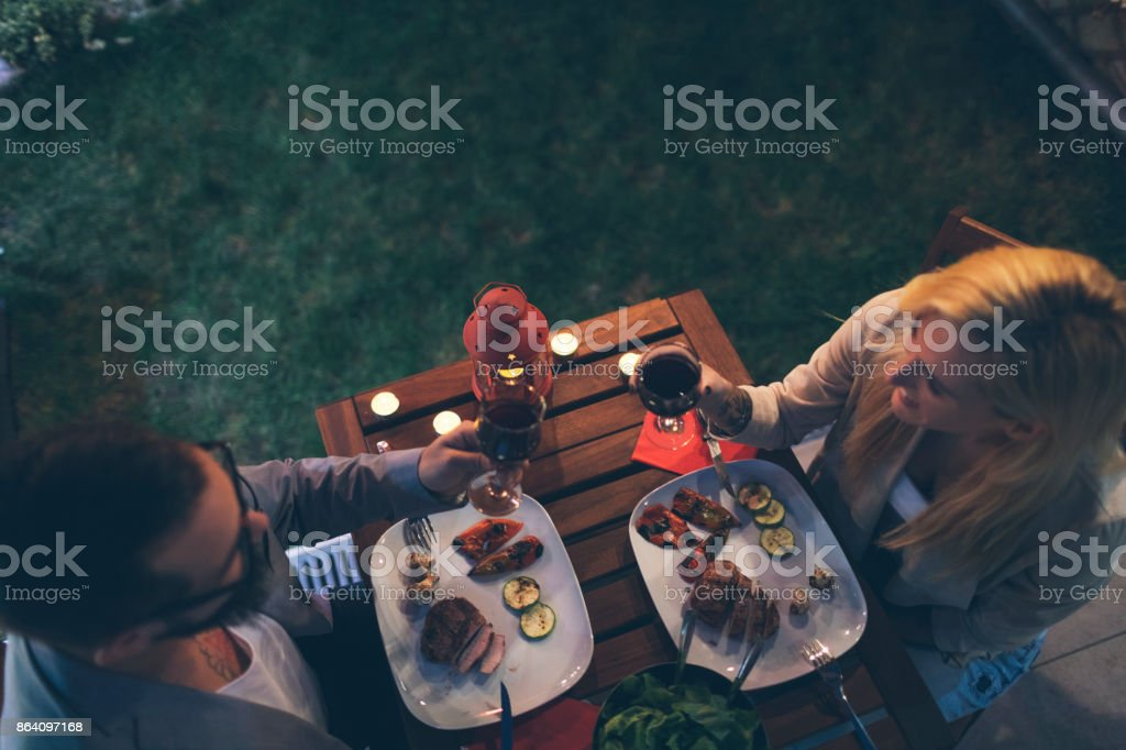 Tattooed Couple Having Romantic Backyard Barbecue Dinner With Proposal stock photo