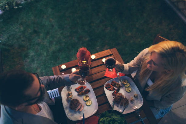 Tattooed Couple Having Romantic Backyard Barbecue Dinner With Proposal Tattooed Couple Having Romantic Backyard Barbecue Dinner With Proposal. Sitting by the table, cheering with red wine and eating dinner date night romance stock pictures, royalty-free photos & images