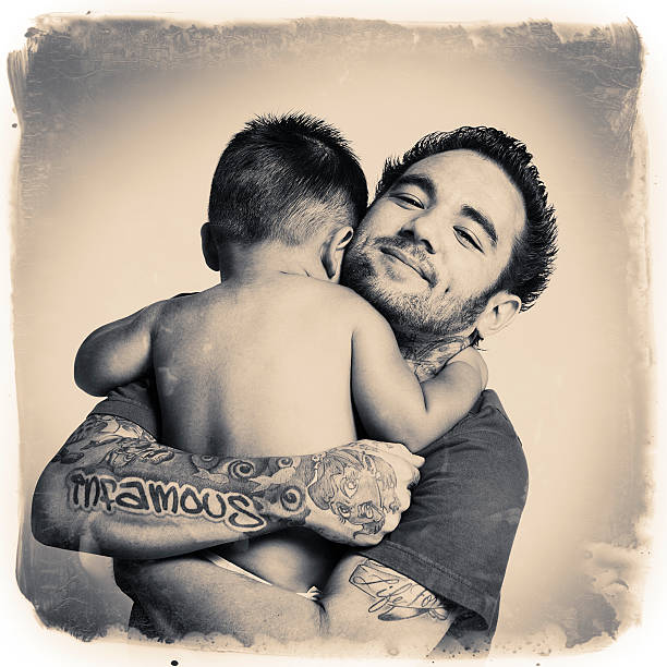 tattooed daddy hug stock photo