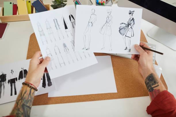tätowierte mode designer holding skizzen - grafik design tattoos stock-fotos und bilder
