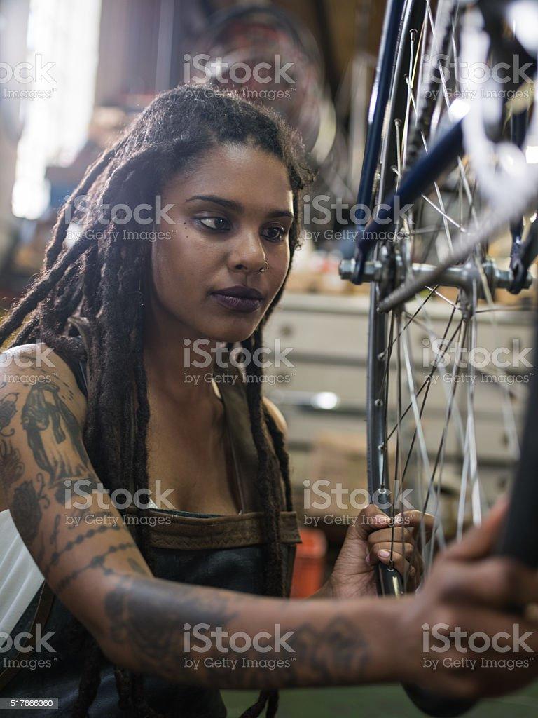 Tattooed female bicycle mechanic working on bike in her workshop stock photo