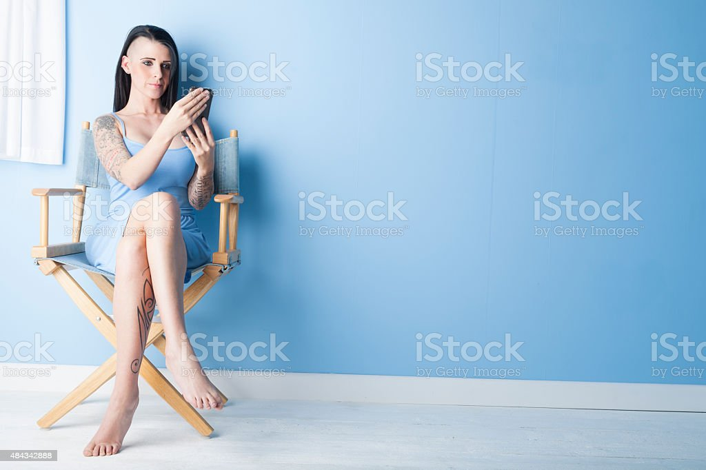 Tattooed Girl Wearing A Blue Dress Looking At Her Phone stock photo