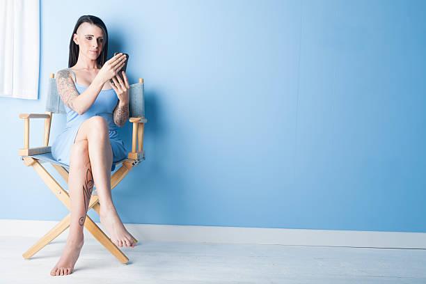 tattooed mädchen in einem blauen kleid mit blick auf ihr mobiltelefon - brustpiercing stock-fotos und bilder