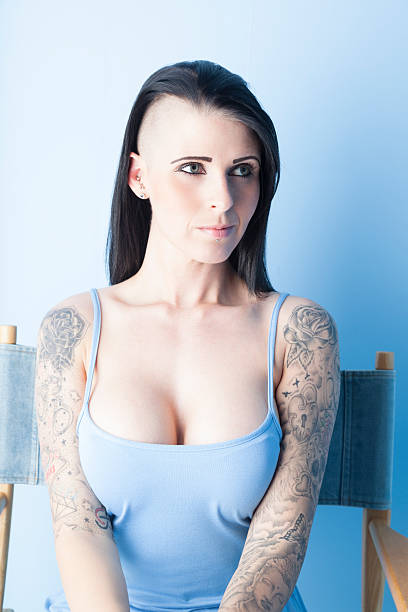 tattooed mädchen in einem blauen kleid mit pastell - brustpiercing stock-fotos und bilder