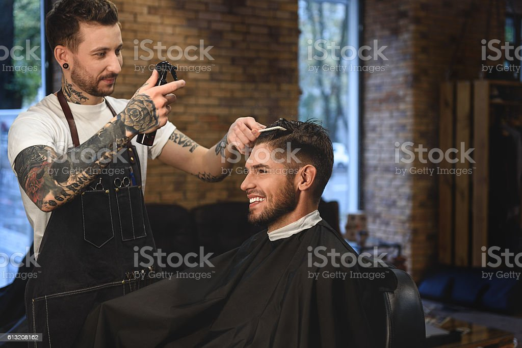 tattooed hair stylist working with a guy stock photo