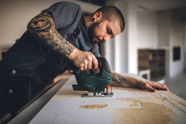 getatoeëerde handy man boren plank en tot vaststelling van de nieuwe houten tafel - zaag stockfoto's en -beelden