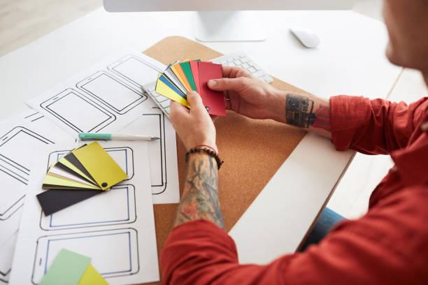 tätowierte männliche designer wahl farbe - grafik design tattoos stock-fotos und bilder