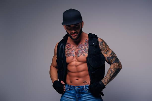 tätowierte männer gekleidet in jeans, cap und weste auf eine nackte t - modedetails stock-fotos und bilder