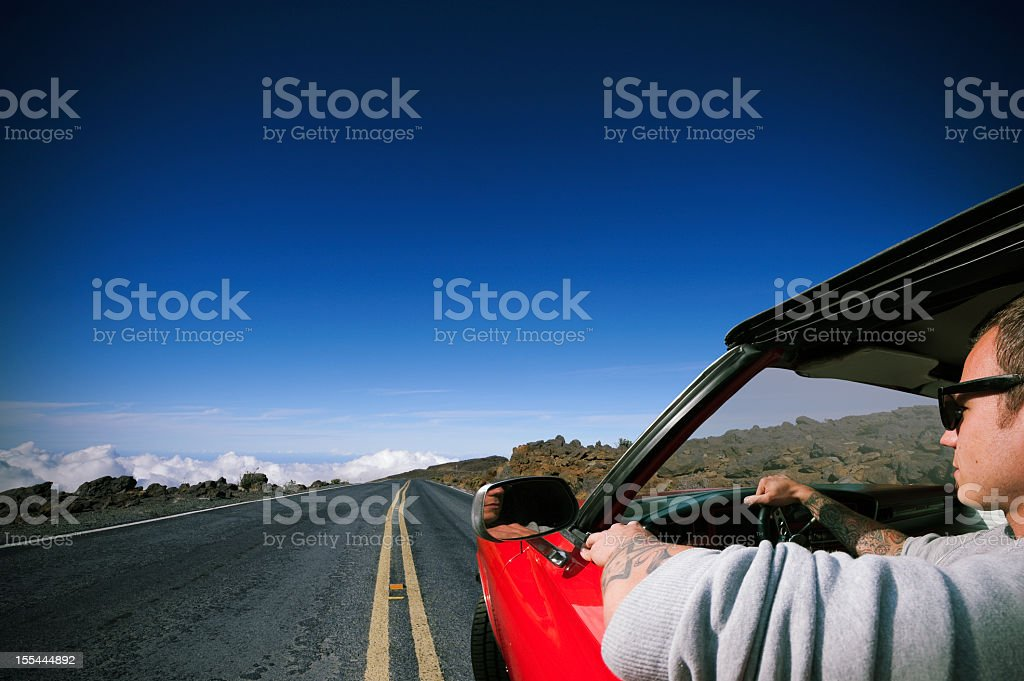 Tattooed man drives red muscle car/ Maui - Hawaii stock photo