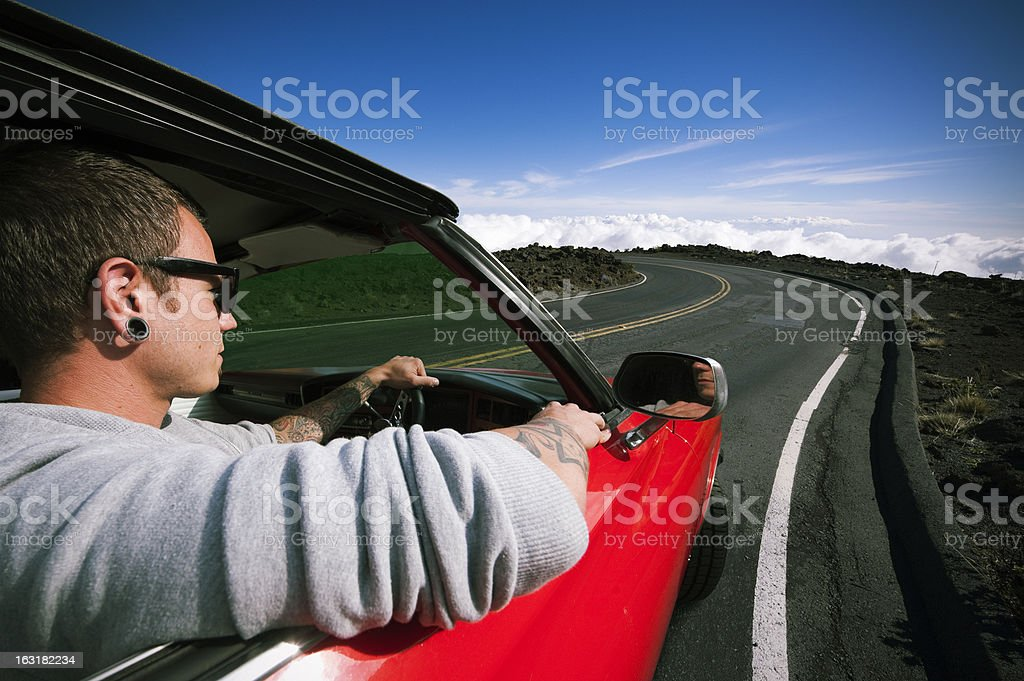 Tattooed man drives red muscle car/ Maui - Hawaii royalty-free stock photo