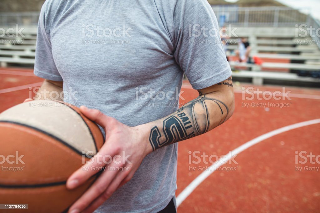Handsome and healthy living man holding a ball at a sports court.
