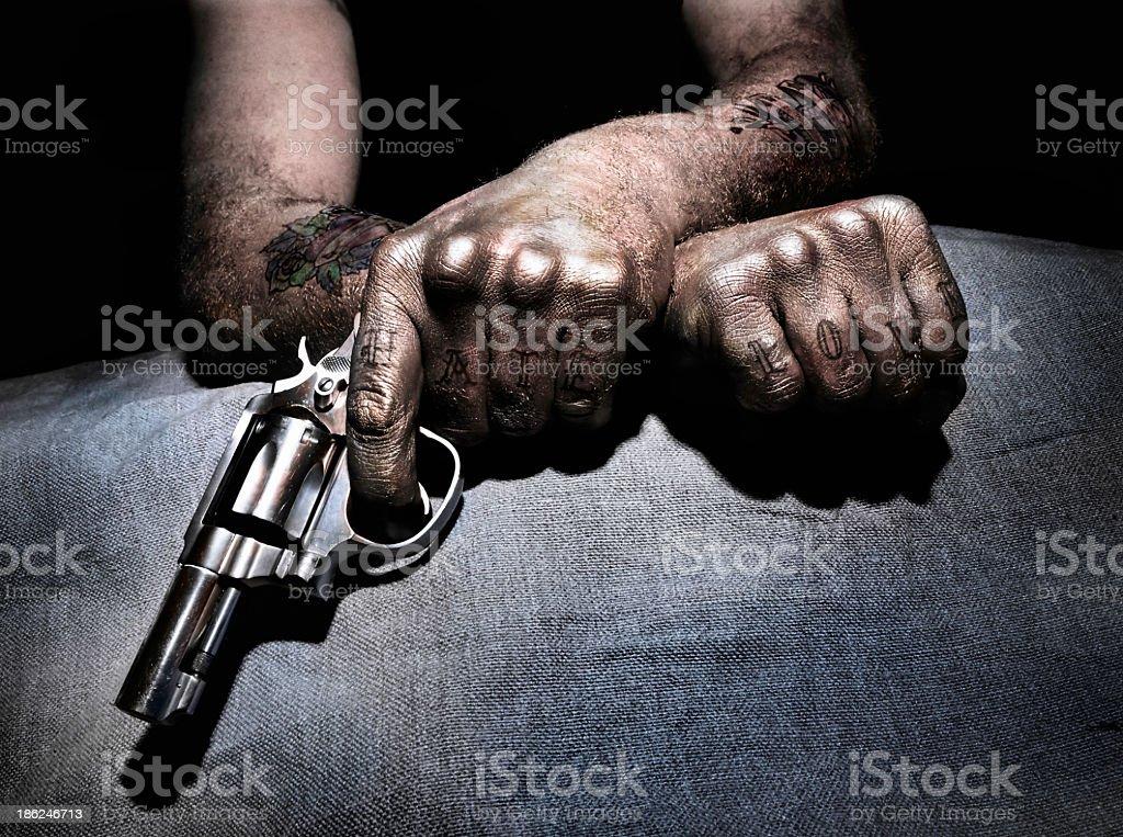 Tattooed man holding a pistol. stock photo