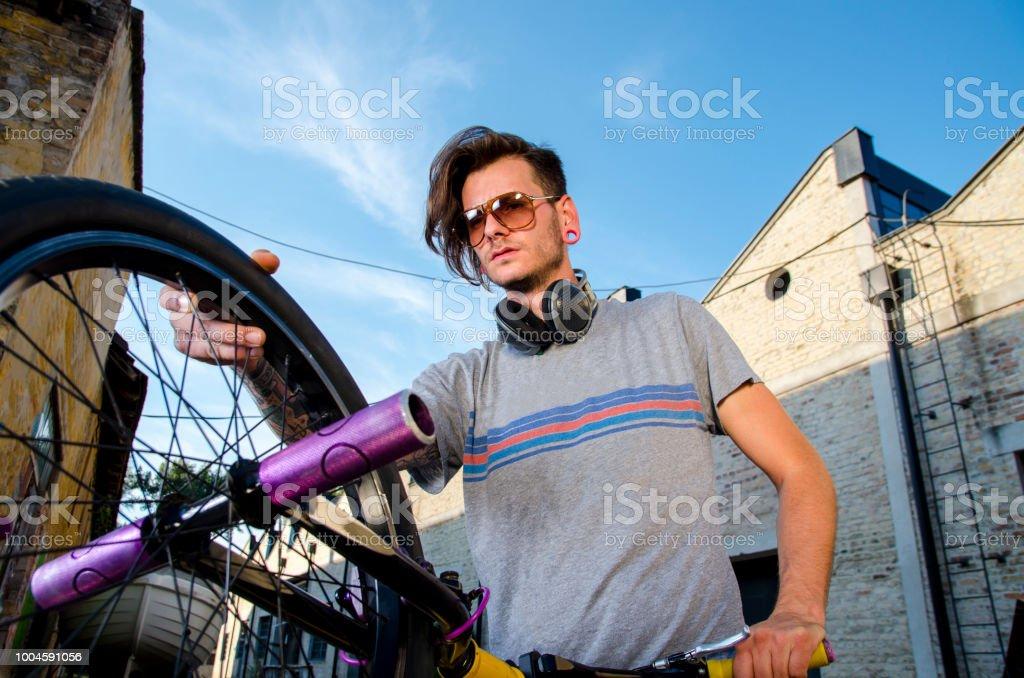 Closeup urban tattooed man holding trick bmx bicycle