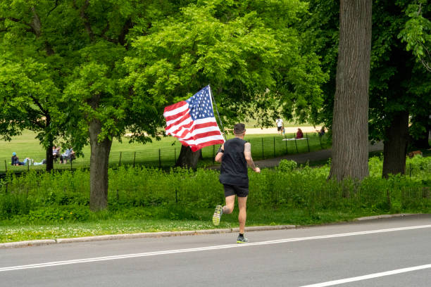 Tattooed Man in Black Jogs Through Central Park While Holding American Flag New York, NY, USA - May 25, 2020: A lone man with many tattoos runs through Manhattan's Central Park on Memorial Day, a national holiday, carrying the American Flag with him. american flag tattoos for men stock pictures, royalty-free photos & images