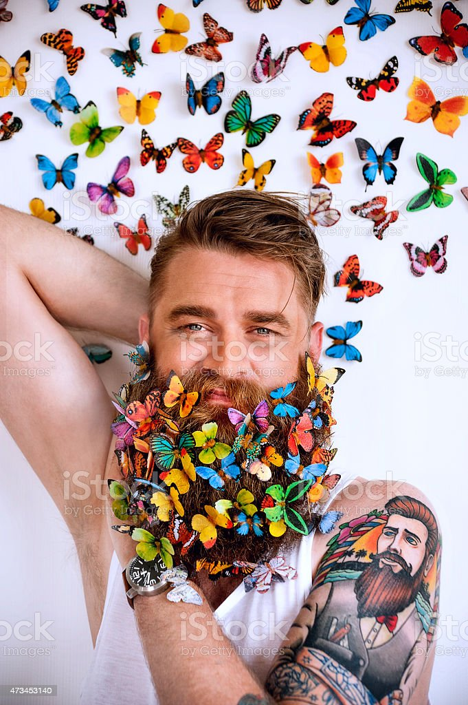 Tattooed man with bright, colorful butterflies in his beard stock photo