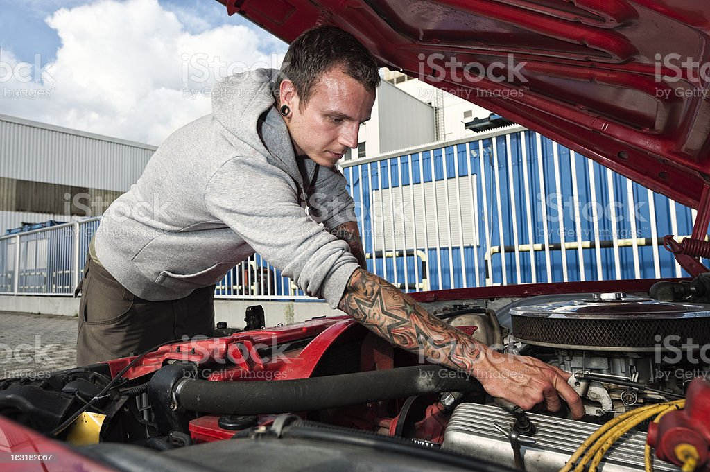 Tattooed man with his red muscle car stock photo