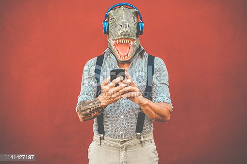 istock Tattooed man with t-rex mask using smartphone while listening music - Crazy senior guy choosing playlist from mobile phone app - Technology trends and madness costume concept - Focus on face 1141427197
