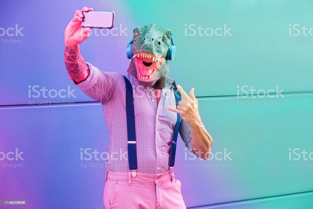 Tätowierter Mann mit t-rex-Maske mit Smartphone beim Hören von Musik-Crazy senior male nimmt Selfie mit Handy-App-Radial lila und blaue Filterbearbeitung-Fokus auf Gesicht - Lizenzfrei Aktiver Senior Stock-Foto