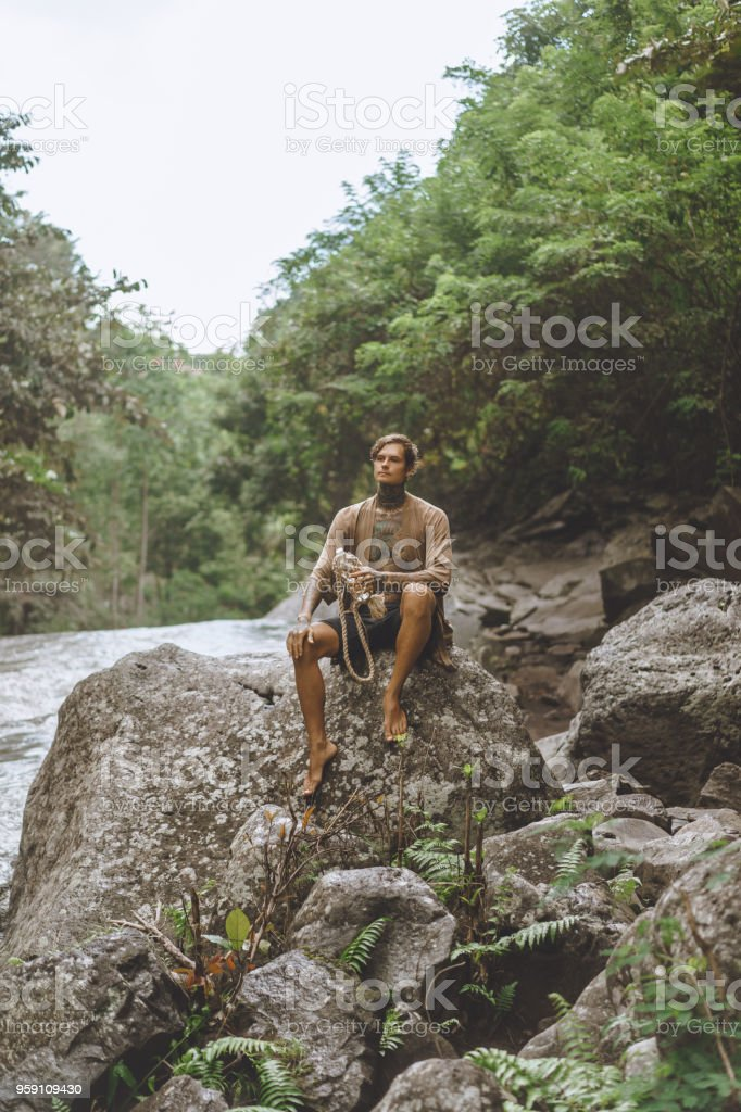 tattooed man with water bottle resting on rock with green plants and...