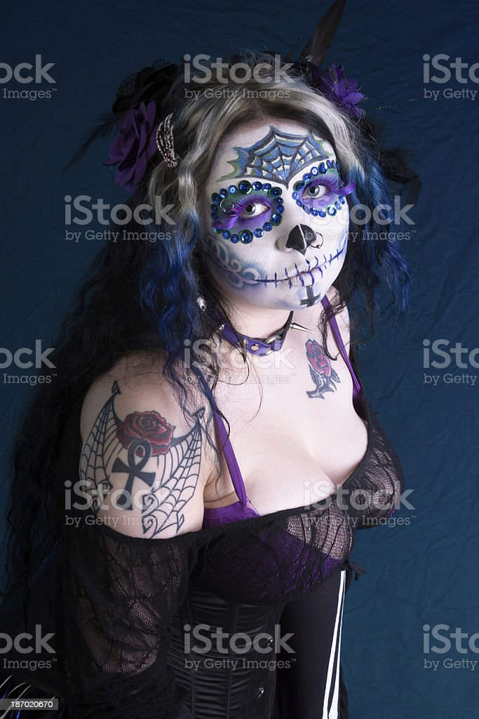 Tattooed model in sugarskull makeup on blue. stock photo