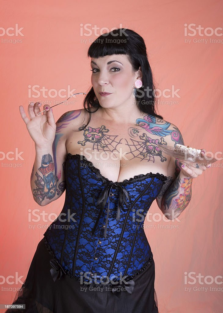 Tattooed pinup model holding empty fork and cheesecake. royalty-free stock photo