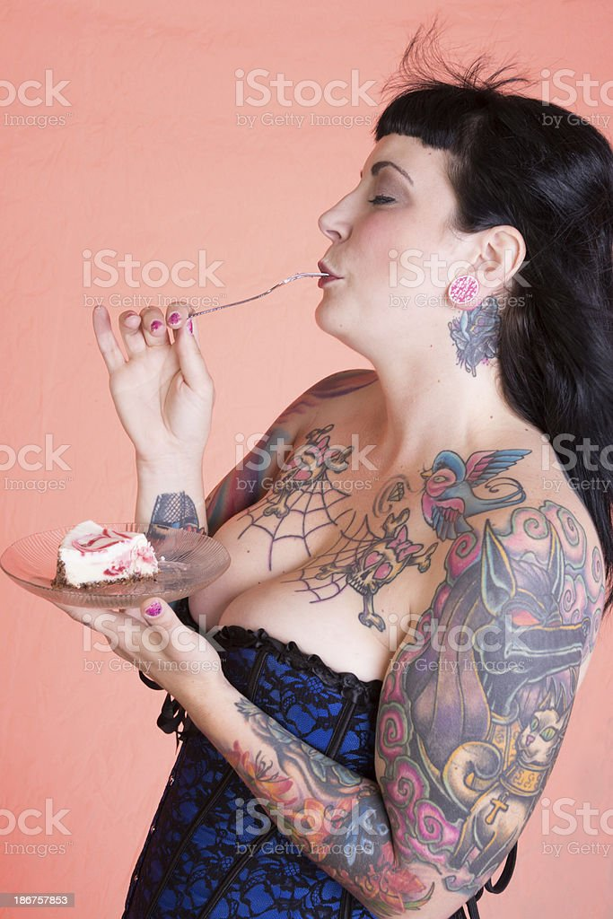 Tattooed pinup model with eyes closed in enjoyment. royalty-free stock photo