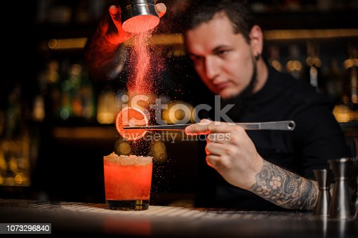 Tattooed professional bartender adding spices powder into a cocktail glass filled with a fresh strong alcoholic cocktail with slice of lemon