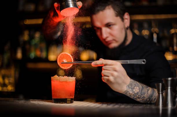 레몬의 조각으로 칵테일 글라스에 향신료 가루를 추가 하는 문신된 전문 바텐더 - bartender 뉴스 사진 이미지
