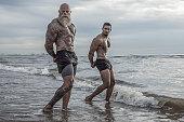 Tattooed Senior Man coaching young man During Workout