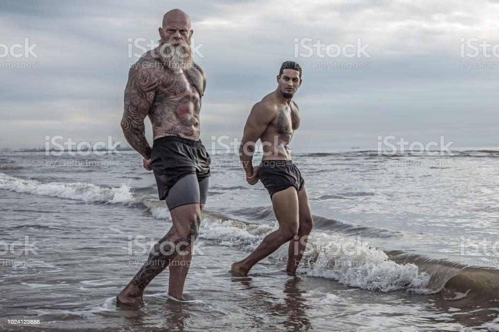 Homem tatuado sênior, treinador jovem durante treino - foto de acervo