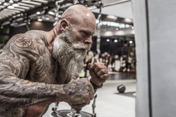 tätowierte senior mann während des trainings - alte tattoos stock-fotos und bilder