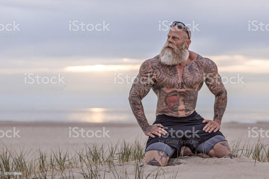 Homem tatuado sênior, durante o exercício - foto de acervo