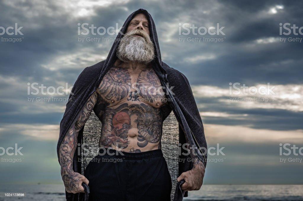 Homem tatuado sênior, posando durante treino - foto de acervo