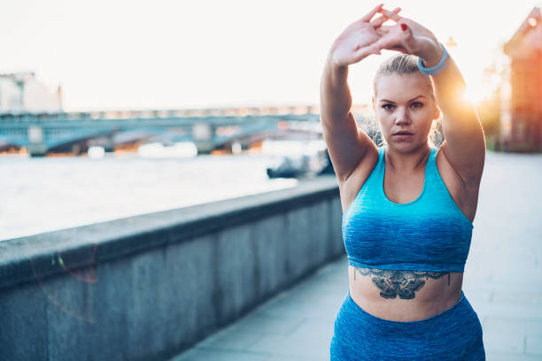 Tattooed sportswoman stretching in the morning stock photo