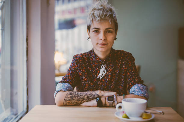 Tattooed woman in a cafe stock photo