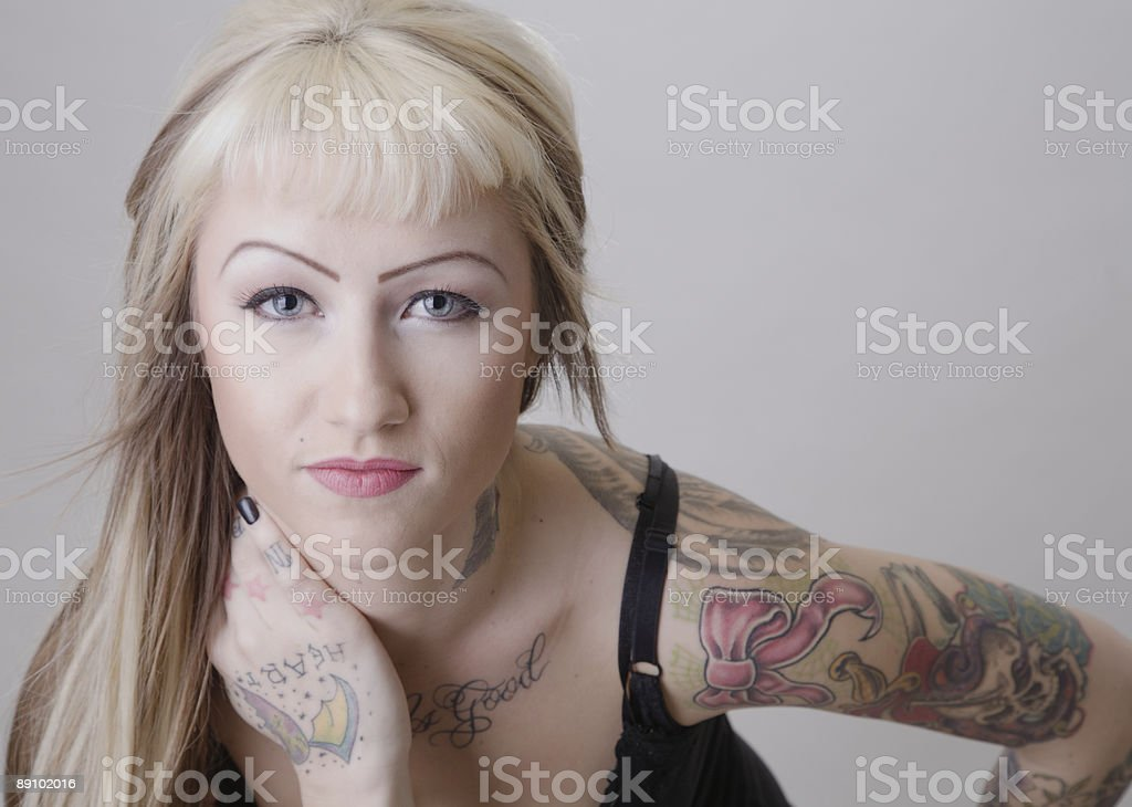 Tattooed Woman Leaning Forward stock photo