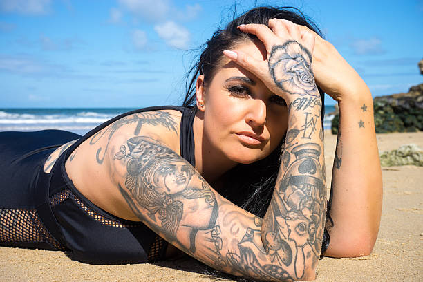 Tattooed woman lying on sandy beach stock photo