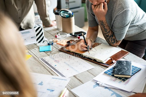 istock Tattooed woman planning a work together 945398668