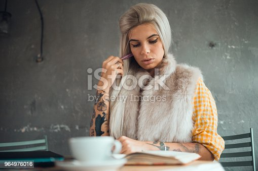1183295518 istock photo Tattooed woman sitting in the coffee shop and writing 964976016