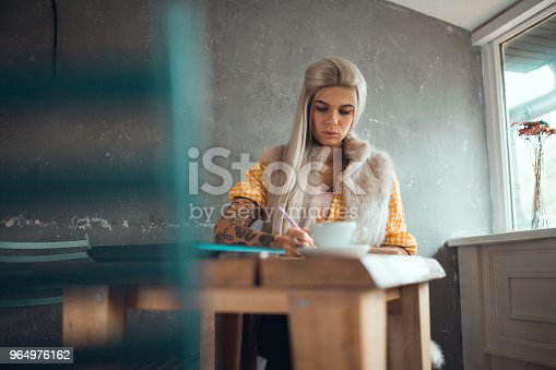 1183295518 istock photo Tattooed woman sitting in the coffee shop and writing 964976162