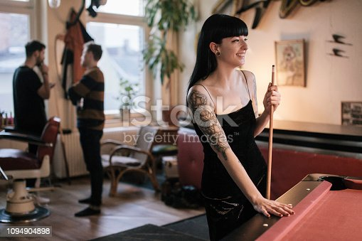 Tattooed woman standing at Billiard Table smiling. Male friends are standing in the background.