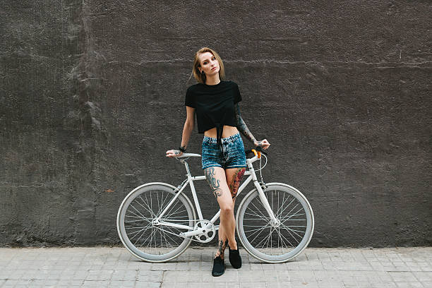 tattooed woman standing in front of white bicycle - tattoo freiheit stock-fotos und bilder