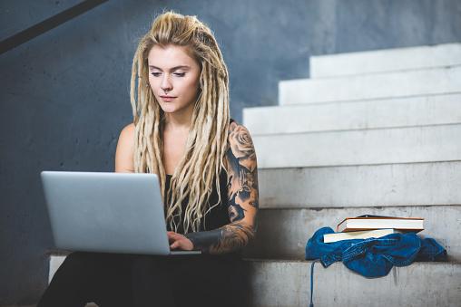 istock Tattooed woman using laptop in university 1011319902
