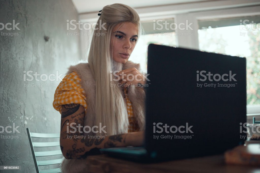 Tattooed woman working and using laptop indoors stock photo